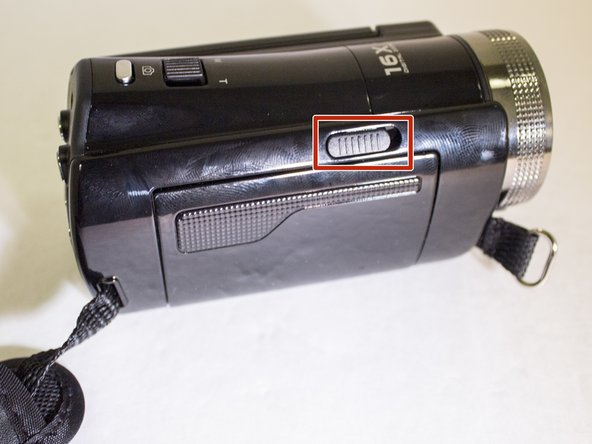 On the side of the camera slide the eject button to the right. This will open the plastic battery door.