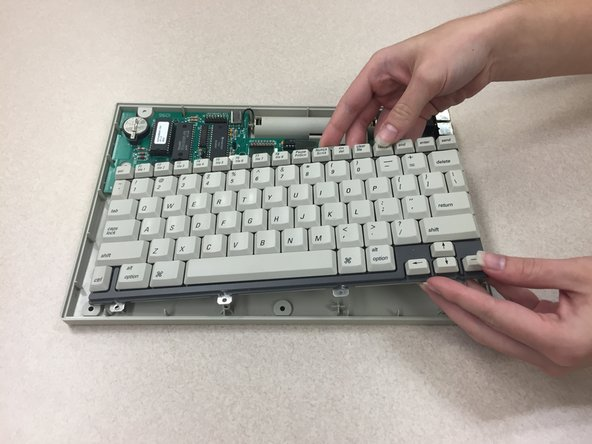 Gently lift the keyboard from the rear panel.