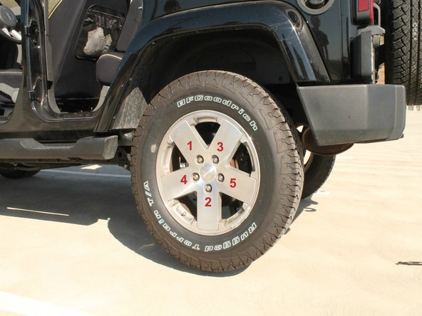 Image 1/2: To physically loosen the lug nuts, use the lug wrench and push down very hard in a counter-clockwise direction.