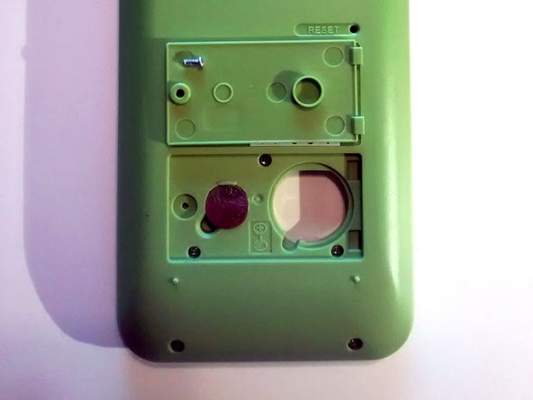 Image 1/3: Fit battery door into the two calculator housing slots. Once placed, the battery door should lay flush with the surrounding green housing.