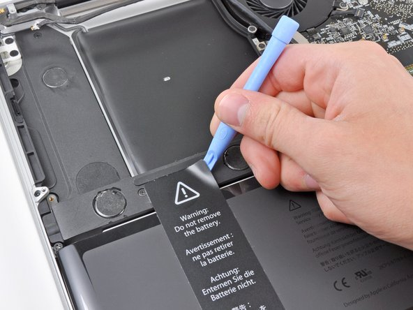 """Use an iPod opening tool or another soft thin-edged tool to carefully lift up a corner of the """"Warning: Do not remove the battery"""" sticker off the right speaker/subwoofer enclosure."""