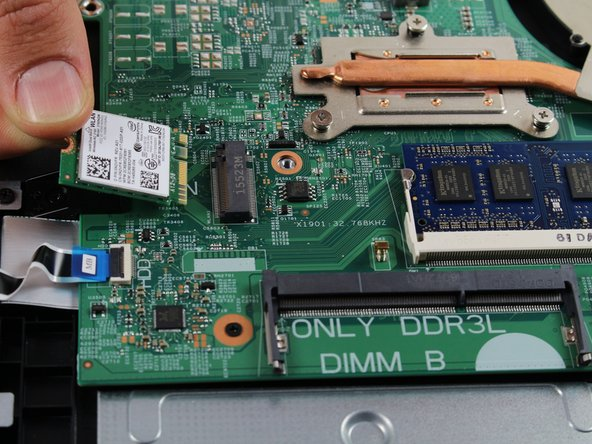 Gently pry the wireless card upward from the screw-side and pull outward toward the edge of the laptop to remove.