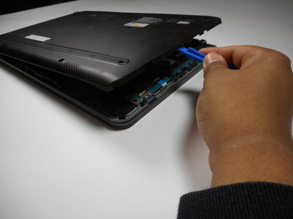 Remove the back panel by inserting the plastic opening tool into the seam of the laptop and pushing downwards.