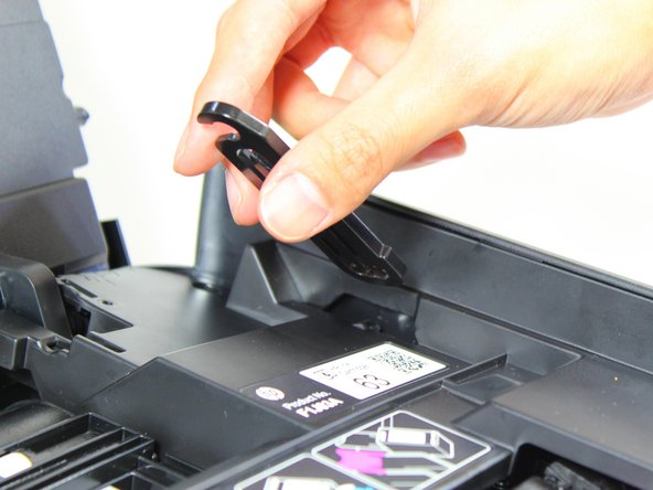 Release the clip by pushing the clip towards the inside of the printer and pulling the clip out.