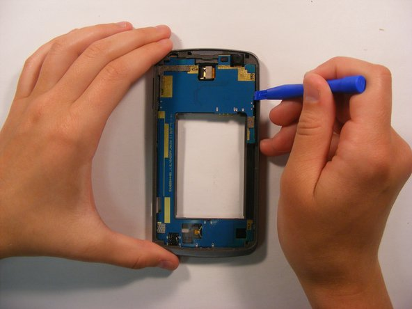Using the plastic opening tool, work your way around the perimeter of the blue motherboard to loosen it from the body of the phone.