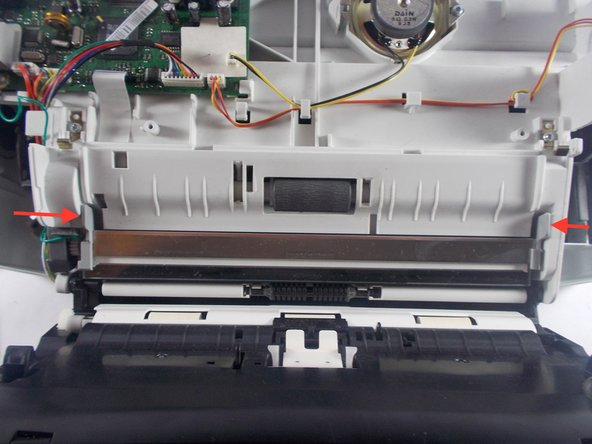 With both cables removed from the main motherboard, carefully push the two grey tabs on the edges of the scanner glass inward (as shown by the arrows in the image). Carefully pull the scanner glass up and out from the device.