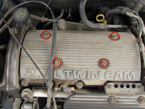 "Use the 1/2"" socket to loosen and remove the four bolts and washers on the spark plug cover labeled 2.4L Twin Cam."