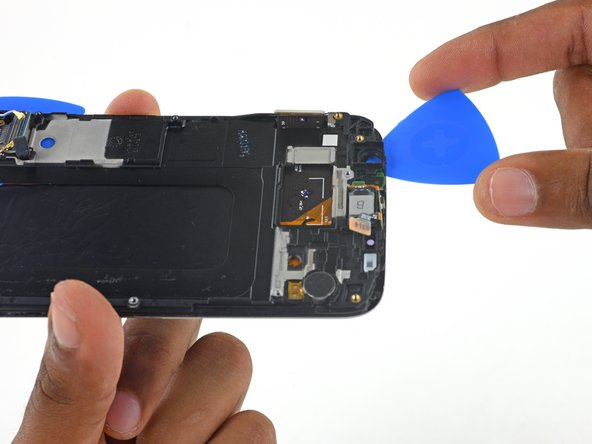 Insert another pick between the display frame and digitizer from the top side of the phone.