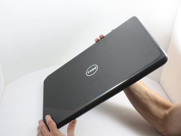 Place the laptop on  a flat surface with the  Dell logo upside down.