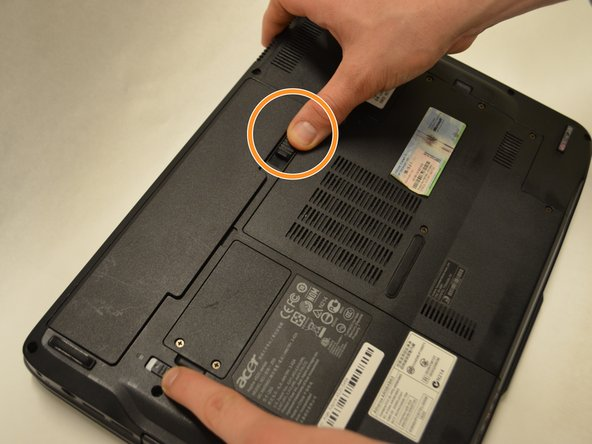 Slide the sliding black tab away from the battery compartment.