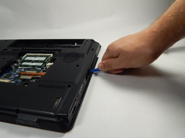 Using the Opening tool, gently pry up the cover and remove it.
