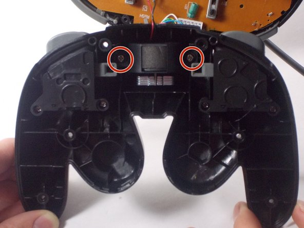 Loosen and remove the 2 screws that are holding the rumble motor in place.