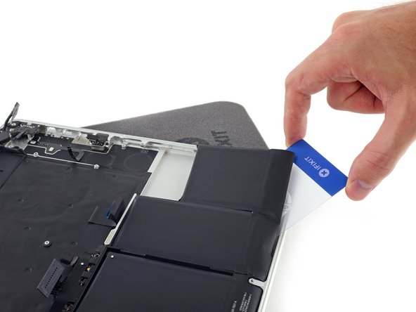 Push the card underneath the second battery cell, and slide it side to side to separate the adhesive underneath.