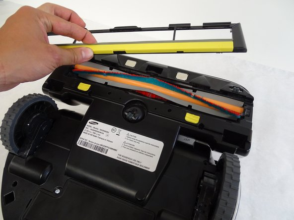 Lift the brush cover, indicated by the yellow strip located above the yellow tabs.