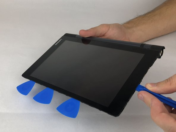 Insert a plastic opening tool under the LCD and gently pry it away from the adhesive. Place opening picks as you go along all four edges to keep the adhesive from sticking again.