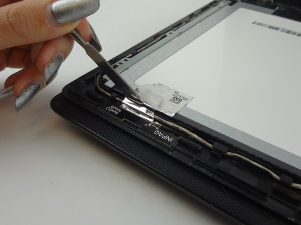 Slice the silver foil tape with a spudger by applying pressure between the frame and the back of the screen case.