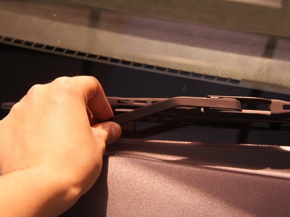 Grab the windshield wiper at the base and lift in a counter-clockwise motion around the hinge, lifting the blade from the window.