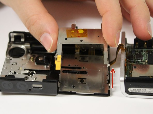 Find the thin, flat orange cable connector that operates the lens barrier and connects it to the main circuit board.