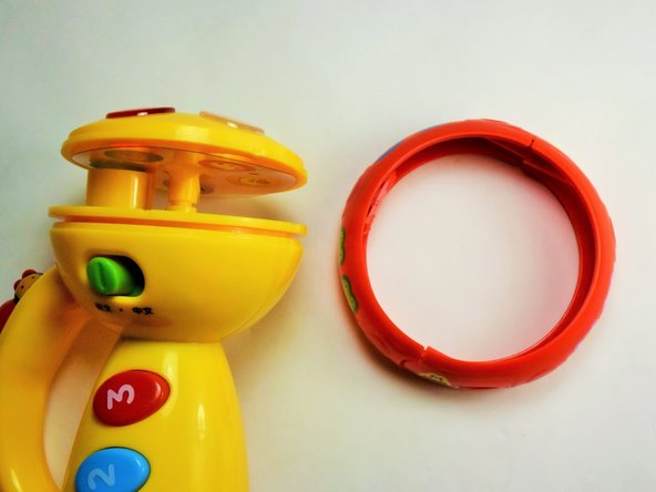 Once the screws have been successfully removed, grasp one half of the ring and pull gently to separate it from the yellow housing. Repeat on the opposite side and the ring is disassembled.