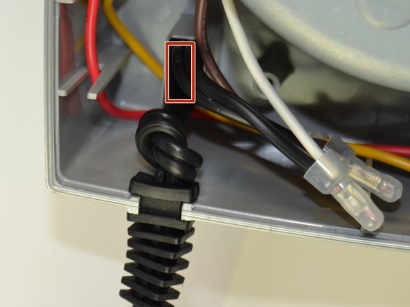 Fit the wires back into the motor base and place the new power cord in the slot.
