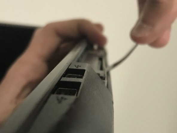 Use the metal spudger to pry upwards on the disk drive until you can grab and remove it.