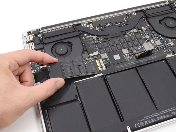 Slightly lift the leftmost side of the SSD and firmly slide it straight away out of its socket on the logic board.