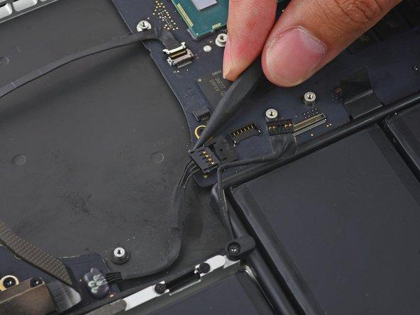 スパッジャーの先端を使って、出入力ボードコネクターの一方を押し出し、ロジックボードのソケットから接続を外します。