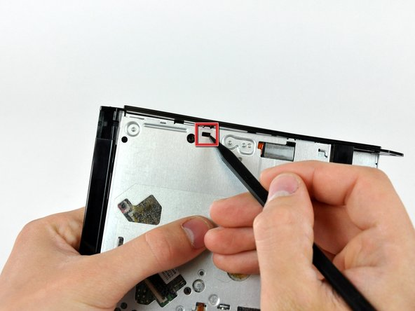 Use the tip of a spudger to push the optical drive bracket tabs out of their slots on the bottom of the optical drive.