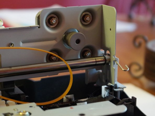 The drive belt can be easily removed by pressing on a tensioner on the other side of the printer. +1 for reparability!