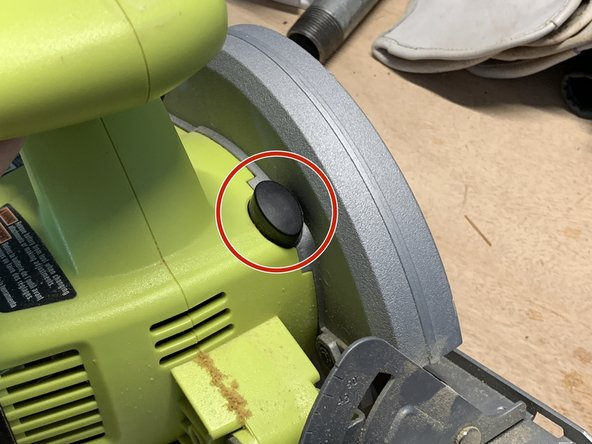 Press and hold down the blade lock button to keep the blade from turning while you loosen it.