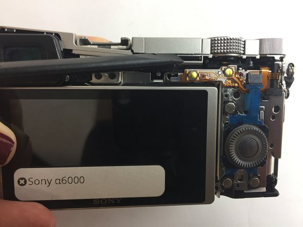 Once the back cover is off, locate the flash of the camera and push it forward to open it
