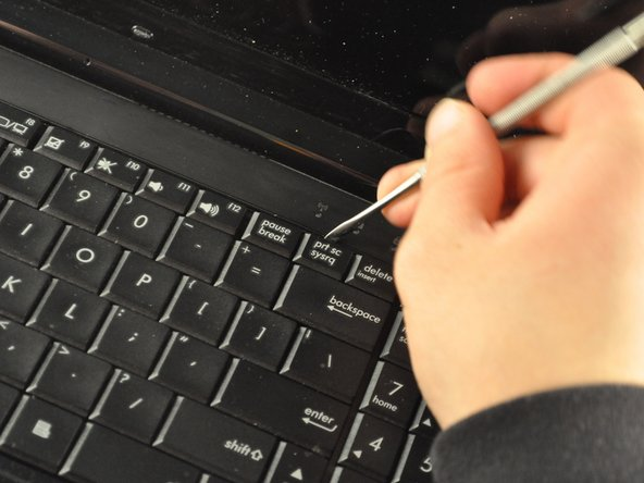 Use the metal spudger or opening tool across the top edge of the keyboard to pop it out.