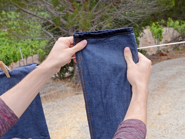 Take the second pant leg and fold the cuff over the line, as you did before. Space this cuff so that the jeans hang as flat as possible.