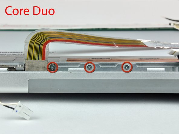 If you have a Core Duo machine, refer to picture 1 and remove three Phillips screws connecting the clutch assembly to the lower edge of the front display bezel near the display data cable.