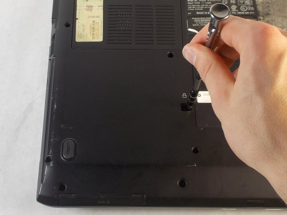 Remove the single 8mm Phillips #1 screw just beneath the lock symbol on the bottom of the laptop.