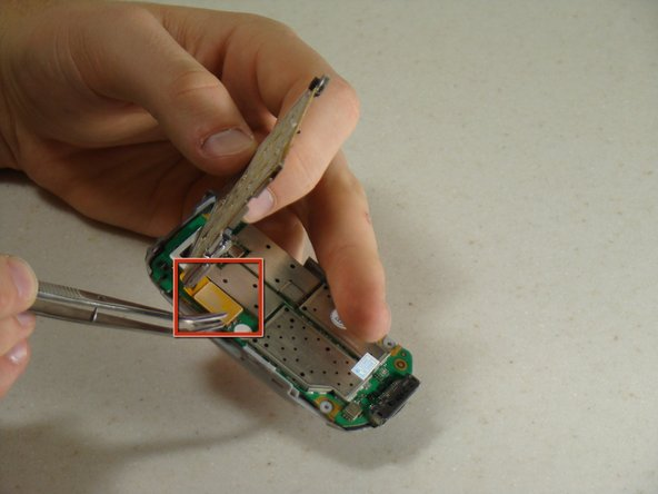 Using tweezers, carefully detach the yellow connector strip from the circuit board by lifting up.