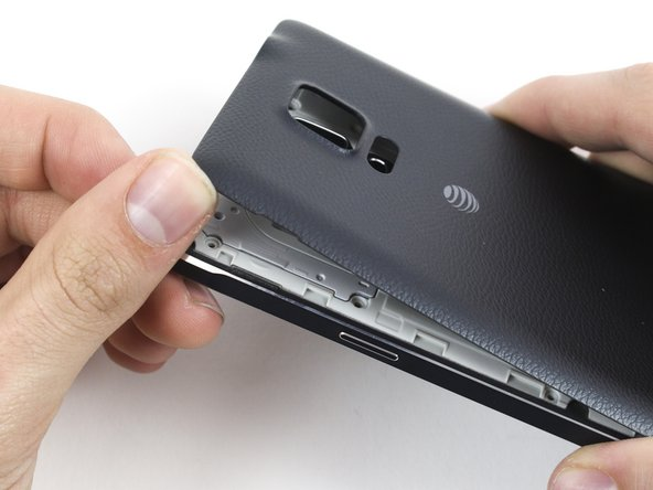Image 2/2: Gently pry and twist the flexible rear cover off the back of the phone.