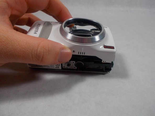With the the camera on a flat surface with the LCD monitor on the surface, lift the front panel of the camera gently up.