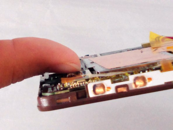 Using your fingernail, flip up the ZIF connector retainer.  If you do not have fingernails long enough, use the black plastic spudger.