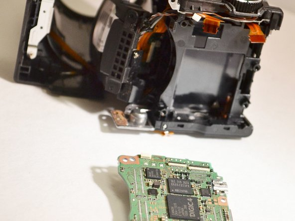 Using the plastic opening tool, lift the tab on the connector and remove the two remaining orange ribbons from green motherboard  (Motherboard is removed).