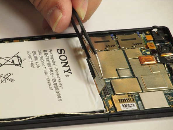 Using the Tweezer, carefully pry open the corresponding chips that are attached to the battery as shown. Then using the spudger, pry the battery away from the phone and watch out for the sticky substance keeping the battery to the phone.