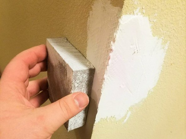 Sand the rough edges of the spackling paste to smooth the surfaces until it is flush with the wall.