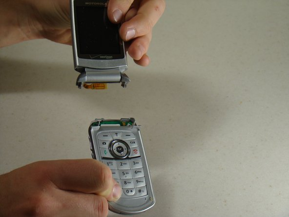 Image 3/3: Carefully detach the two sections of the phone.