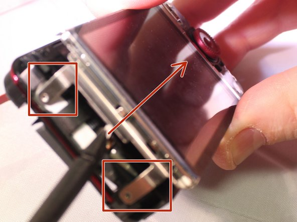 Use a spudger or plastic opening tools to pry up the LCD screen and free the two metal tangs on the left side. Reference the second image.