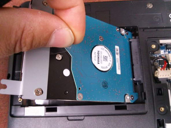 Image 2/3: Lift up on the clear flap, and then pull back on it to remove the hard drive.