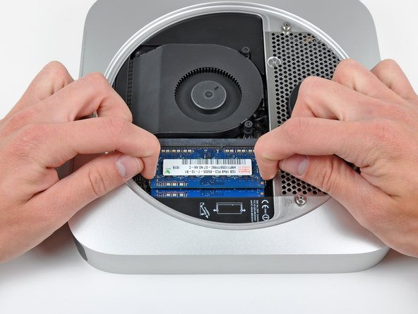 Image 1/2: Release the tabs on each side of the RAM chip by simultaneously pushing each tab away from the RAM.
