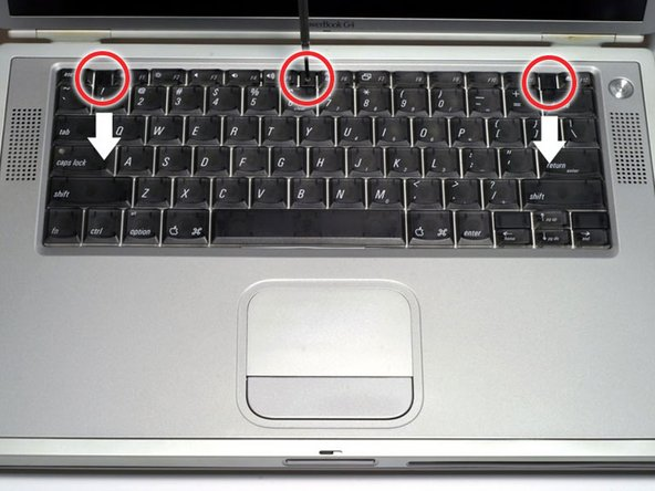 Image 1/1: Pull the keyboard release tabs toward you and lift up on the keyboard until it pops free.
