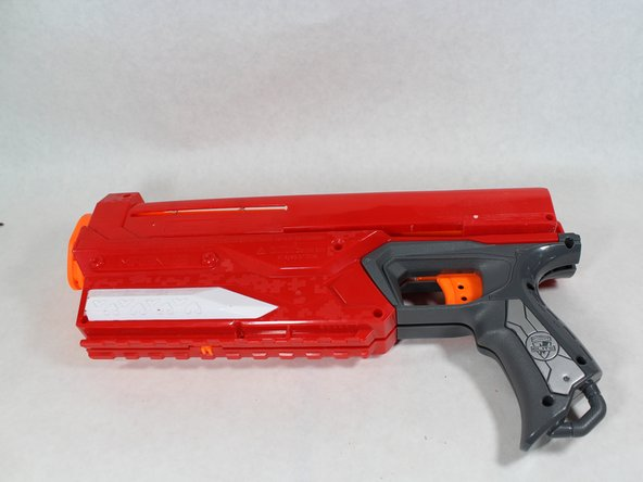 On the same side, remove all (9) screws from the body of the blaster as shown.