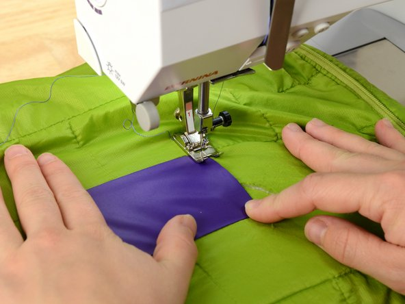 Slide the garment into the sewing machine, repositioning the patch if necessary.