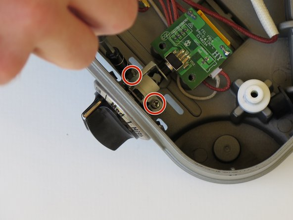 Remove the two 6 mm Phillips #2 screws that secure the white plastic LED holder.
